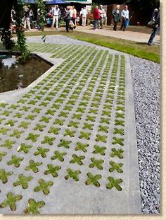 Cross-stitch pattern using grass as the thread and concrete as the fabric.     Grasscrete® is a proprietary system that relies on placing disposable plastic 'pots' at equal spaces over a prepared base and then pouring concrete to fill the spaces in between the 'pots'. A soil mix and seed is then added to fill the resulting voids.