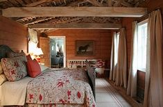 Wide horizontal wall panels and a bed made up in crewel fabrics define cozy barn chic.