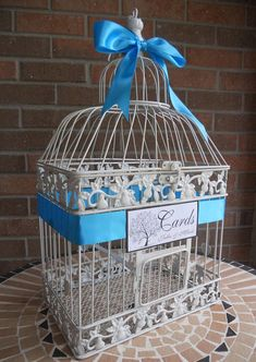 """Bird Cage Wedding Card Holder, Shower Cards, Anniversary, special event. Antique White Cage shown with Turquoise Satin Ribbon & Tree of Life Card. Measures 19"""" tall, 10 wide, and 7"""" deep. Will hold approximately 100 to 125 cards, depending upon size and thickness of cards. Cards can be"""