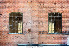 Broken windows on an old and abandoned industrial building. The old factory is made of red brick. - Stock Image