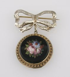 A 19TH CENTURY MICRO MOSAIC PENDANT depicting an arrangement of flowers against a black ground, within a yellow metal rope-twist frame, bearing crosskeys hallmark, with a later silver gilt ribbon-tied brooch