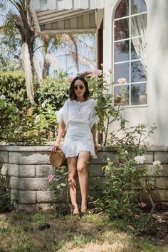 Aimee Song of Song of Style wearing a white wrap dress. White wrap ruffle dress+olive green slide sandals+round rattan crossbody suede bag+gold necklace+earrings+sunglasses. Summer Casual Outfit 2017