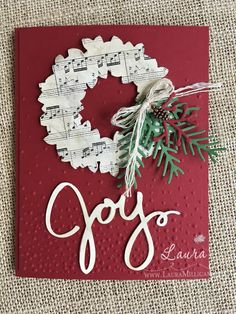 handmade Christmas card by Laura Milligan ... die cuts and embossing folder texture ... wreath cut from sheet music ... Joy with script font ...  fir boughs ... traditional colors ... Stampin' Up!