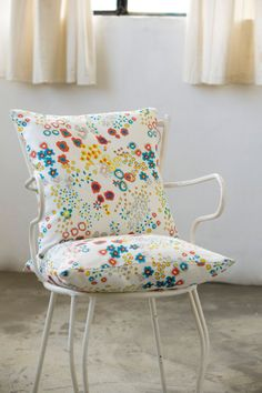 Colorful cushions cheer up a simple chair.