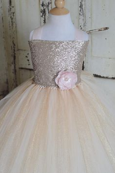 This amazing new design is made with a sequence gold top lined with satin for comfort with blush corset straps that ties in the back into a bow, embellished With a large blush flower and a full tulle skirt in champagne and glittery gold. This dress is customizable to your theme or event please see our color swatches for tulle in this link below, tops and flowers come in other colors please convo me with your request. https://www.etsy.com/listing/193270312/custom-order...