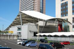 ユニバーサル・スタジオ・ジャパンの玄関口、ユニバーシティ駅を28枚の写真と建築データで紹介。白い帆の屋根と楕円状に張り巡らされた構造材のコントラストが繊細。