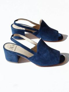 Versatile and chic navy suede sandal with a delicate, elasticized back strap and low heel. Peep toe. Fully lined. Material: Lamb suede upper with stacked wood heel and natural leather sole. Handmade i