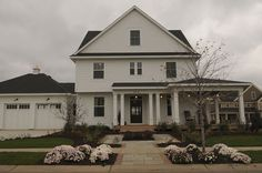 Matt Shimon and Mike Cuthbert built an updated version of the classic farmhouse with clapboard siding and a wraparound porch. The carriage-house style garage is topped with a cupola.