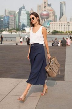 Amlul in a navy midi skirt, white tank, and clear heels