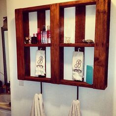 shelf for our bathroom made out of an old pallet. We sanded the wood, stained it, then added hooks to the bottom to hang towels on! Very inexpensive! Love it!