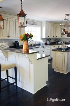 We spend a lot of time in our kitchens and think they should be beautiful!  This kitchen features antique white cabinets with brown and black granite, and copper lanterns (the lanterns are actually outdoor lanterns, but their scale works well over this eat-in breakfast bar).  We hit HomeGoods for canisters, cutting boards, and other storage and decor pieces to finish off the space. {Sponsored by HomeGoods}