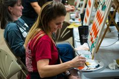 A military spouse loads her paintbrush during a Painting with a Twist event, Oct. 21, 2017, at Moody Air Force Base, Ga. (U.S. Air Force photo/Erick Requadt)