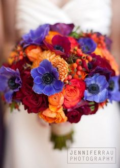 Purple anemones pop against a bouquet of orange ranunculus and hypericum berries. Fall Wedding Bouquets