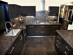 The backsplash is an Italian glass mosaic blending charcoal grays and browns with an iridescent finish of pewter.