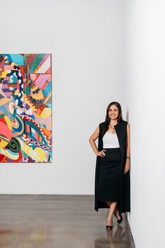 Garcia wears a long vest and pencil high rise skirt by Zero+Maria Cornejo, silver and diamond necklace, and black peep toe pumps by Damico Milano, all from Allora by Laura (1269 Coast Village Rd., 805/563-2425, allorabylaura.com). The painting behind her is why do boob vases lactate inside a tesseract rotating aimlessly in hyperspace?, 2015, by assume vivid astro focus. Photo by Cara Robbins.