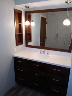 Walnut vanity and mirror. Glacier white corian vanity top. To be fair, only the frame of the mirror is walnut, the reflective part of the mirror is mirror.