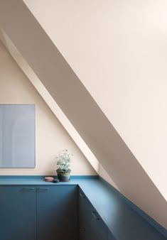 All walls and ceilings in this apartment are painted in apricot pink and sandy beige tones, while storage units and kitchen work surfaces are a blue-grey colour.