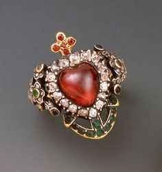 This ring in gold and silver contains a heart of garnet surrounded by diamonds and other precious and semiprecious small stones, 19th  century - a cross camarguaise having a core and an anchor.