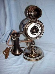 The candlestick telephone was an upright desk phone that was in use during the days of manual switching. Later models, like the one pictured here, were adapted for automatic switching, and had a dial set on the base. The early rotary dials had eleven digits, with one digit set aside for dialing long distance. Though the long distance digit was essentially a second zero digit on the phone, it was placed there to reassure users that dialing a number with zero in it would not lead to the…