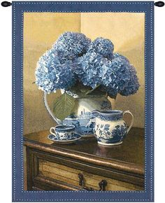 Woven in North America History: Blue Willow tapestry features a peaceful scene where we see a wooden side table with a vase of fully bloomed blue flowers sittin