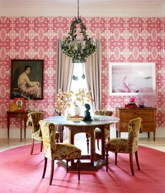 A very pink dining space with pattered wallpaper and traditional furniture