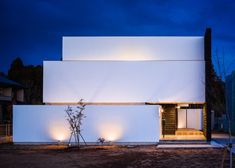 A tall white wall wraps around the base of this house in Tsukuba City, Japan, screening it from the street and creating the illusion of a triple-level structure