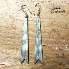 > sleek arrowhead shaped earrings in silver metallic <