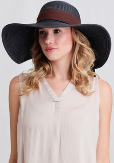 Create an instantly glamourous look with this navy, woven straw hat designed with a large floppy brim and accented with a large brown bow at the crown.