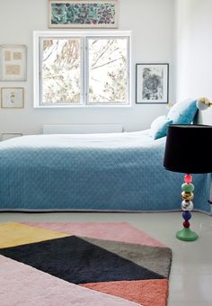 Colorful and bright bedroom with pretty artworks, blue bedspread and a multicolored rug.