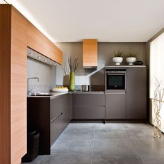 L-shaped kitchen with grey cabinetry, veneer units and grey flooring