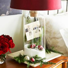 holiday cheer bedside lamp: transform a clear glass lamp base or a large vase into a festive still life with a few accents. fill the bottom with epsom salt and arrange a scene with small ornaments, pine branches, and old photographs or cards. Christmas Card Display, Christmas Lamp, Simple Christmas, All Things Christmas, Winter Christmas, Christmas Decorations, Christmas Vignette, Merry Christmas, Christmas Bedroom