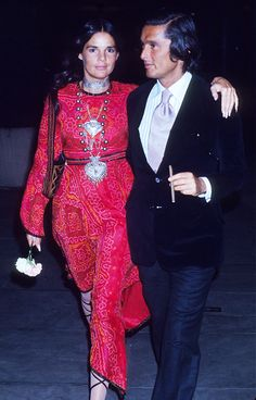 Ali MacGraw in a printed red maxi dress, statement jewelry, and lace up shoes