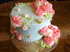 Light blue and pink buttercream flower cake I would not put all the flowers on. One on the top to you right. The ones on the left bottom and left upper side.