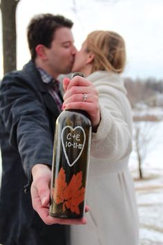 Wine-themed wedding save-the-date engagement photo.  Made with a silver sharpie & spray painted a leaf stencil on a de-labeled wine bottle.