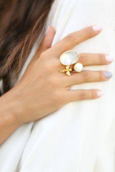 https://www.cityblis.com/2069/item/7335 | The Angel Ring - $108 by Toosis | This Ring is hand crafted with pure and sterling silver. The gold color is done by coating silver with 18karat gold. This ring is designed with a clear white quartz stone, a coin pearl and diamond like zircon stones on the wings of the angel.  Size: It will take 7 days to prepare after your order.... | #Rings
