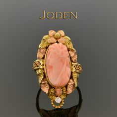 Coral cameo rings are warm lovely carvings from a unique medium. The pink fleshy tones of the coral bring to life the subject in an interesting way that make this ring really stand out. Surrounding the bezel set cameo are 14 karat yellow, green and rose gold leaves with a single rose gold flower at the top. The rose gold perfectly compliment the coral and a single unexpected round brilliant cut diamond, that has a weight of approximately .02 carat, at the bottom complete this design.
