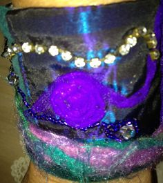 I made this wrist cuff using pieces of an old prom dress, yarn, part of an old belt, beads, other fabric and ribbons. I love it.