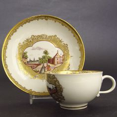 MEISSEN. c.1745 – 1755. German Hard-Paste Porcelain.  An 18th Century Meissen Porcelain Teacup and Saucer with Hausmalerei Decoration. Painted with Well Dressed People in a Town or Village, with a Complex Gilt Border