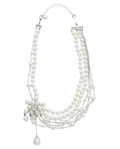 A starburst floral design leaves a trail of white glass pearls and crystal accents to adorn this multi strand necklace creating a look that is chic, sophisticated and stylish.  $69.00