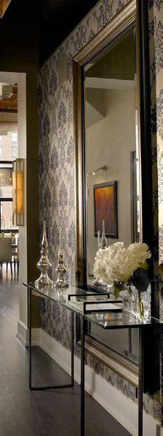 In this hallway, you can see the chic & sophisticated decorating style from the interior designers, James Dolenc and Tom Riker — from James Thomas Chicago. The oversized mirror enhances the design idea.