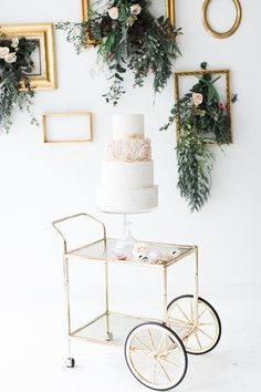 A vintage bar cart with gilded accents brings all eyes to this feminine cake thanks to uncluttered décor, save for a few elegantly scattered roses.