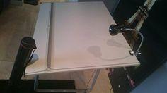 mesa de desenho preta da tok&stok, com cobertura de plastico emborrachado e tachinhas para fixa-la, mais luminaria dobravel flexivel branca tech tubular de metal com lampada fluorescente mesa desenho fixada no canto da mesa ...
