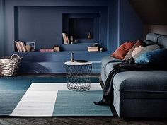 A flatwoven rug in green-blue and white block pattern, shown in a living room together with a dark grey three-seat sofa.