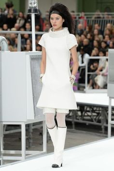This dress from Chanel's fall 2017 collection is inspired by styles from the 1960s. The cold war influenced fashion greatly in the 1960's. Space age clothing was all the rage. Andres Courreges was one of the most influential space age designers. This dress has a similar silhouette to those popular in the 60s as well as being paired with those boots and the collar that looks like it was made to have a space helmet attached to it. Camilla Costa Goetz