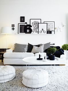 light sofa, pattern grey pillows, shelf with posters