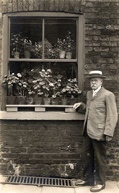 Victorian or Edwardian black and white photo of man outside his house with flowers behind window