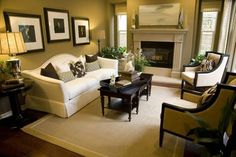 Greenish-brown walls wrap around this living room with fireplace, white sofa, two armchairs, dark wood coffee table, beige area rug with light green border placed on hard wood floor. Bedroom Decor Cozy, Spacious Living Room, New Living Room, Trendy Living Rooms, Furniture Color Schemes, Dark Wood Floors Living Room, Living Room Wood, Cozy Living Rooms, Rugs In Living Room