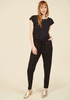 <p>Playing with statement pieces is nice, but exploring your outfit imagination with this basic black jumpsuit is where the real fun lies! With seamless short sleeves, a drawstring waistline, pockets, and tapered legs, this knit onesie sets a solid foundation for showcasing your treasured shoes and accessories.</p>
