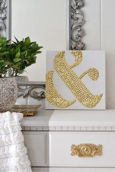 Bild mit Symbol auf Leinenwand mit Reiszwecken in Gold