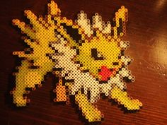 Jolteon is approximately 8 in high by 8 in tall. Made of fused Perler Beads.
